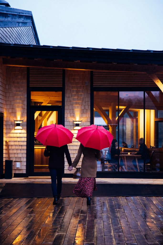 newly wed couple using red umbrellas