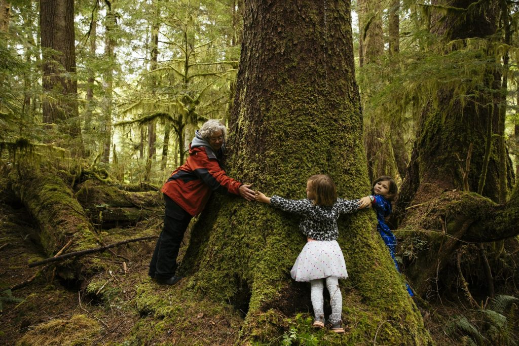 Family hugging a moss-covered tree