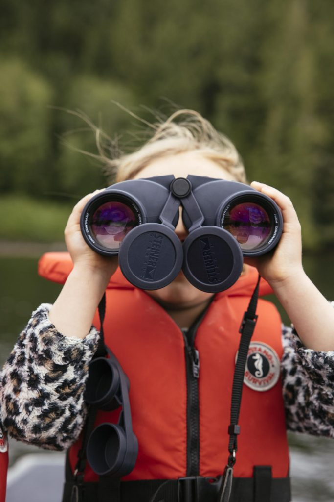 Girl with binoculars on a boat